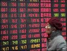Woman in front of Shanghai market indicator board