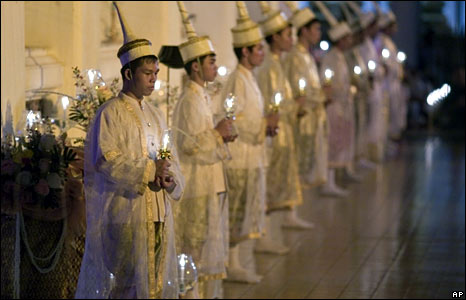 Thai performers in traditional dress carry candles in a Buddhist ceremony in Bangkok