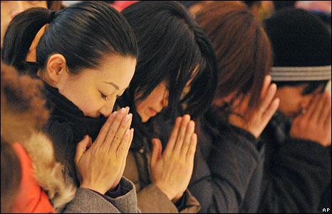 Women pray at Tokyo's Zojoji Buddhist temple