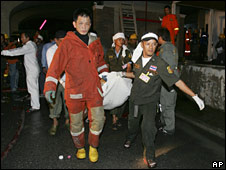 Rescue workers carry a body from the Bangkok nightclub