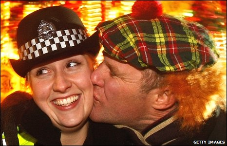 Police constable Lee Dingsdale receives a kiss from Aiden Cooper in Edinburgh during the Hogmanay celebrations