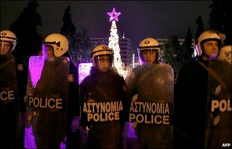 Riot police stand in front of the Christmas tree outside the parliament building in Athens during New Year celebrations and simultaneous demonstrations, 1 January 2009