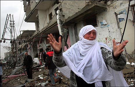 A Palestinian woman cries amid destroyed buildings in Rafah refugee camp, southern Gaza