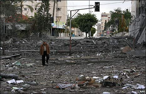A man walks amid the ruins of a Palestinian Authority parliament building in Gaza City