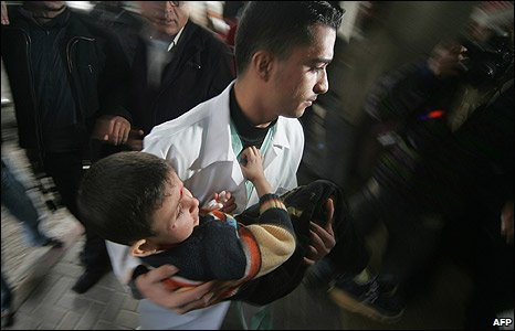 A medic carries a wounded boy in Gaza City's Al Shifa hospital