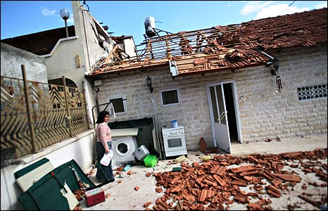 An Israeli woman outside her house in Sderot bombed by Hamas militants