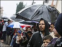 Filas de personas en Gaza bajo la lluvia