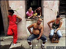 People sit in front of their house in Santiago, Cuba