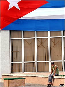 A Cuban man sits in front of a large Cuban flag