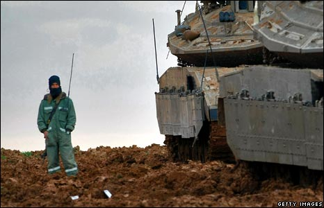 An Israeli soldier stands guard over his unit's tanks at a forward deployment base near Gaza