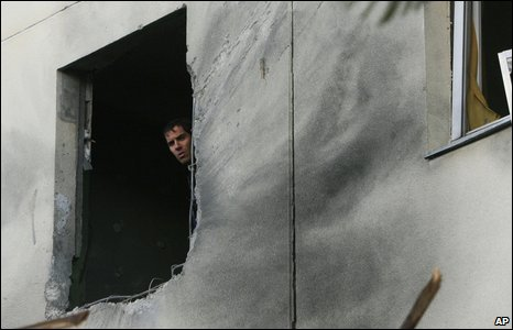 An Israeli man inspects the damage to a building in Ashkelon, caused by a rocket fired by Palestinian militants from the northern Gaza Strip, 2 January 2009