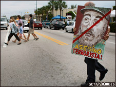 A man crosses the street in Miami holding a painting of Cuban President Fidel Castro that reads: 'Assassin terrorist'.
