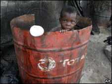 A boy plays inside an oil drum at the waterfront in Lagos, Nigeria