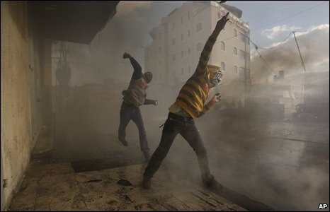 Palestinian protesters throw stones at Israeli troops during clashes at a demonstration in Shuafat refugee