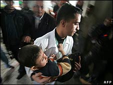 Palestinians carry a wounded boy into Gaza City's Shifa hospital