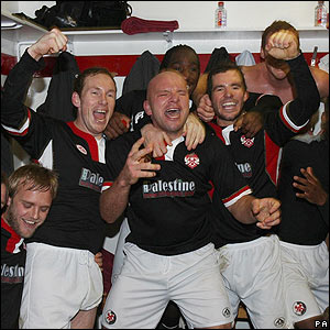 Kettering's players celebrate in the dressing room a