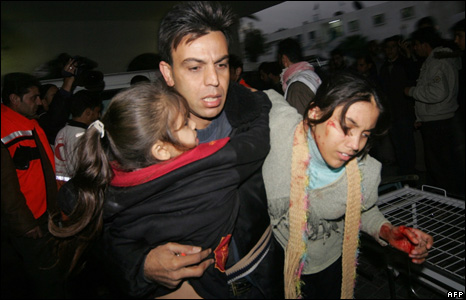 A Palestinian father carries his two wounded daughters into a hospital in Gaza City (4 January 2008)