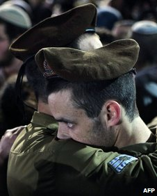 Israeli soldiers comfort each other at the funeral for a comrade on 4 January