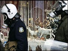 Riot police walk past a Christmas-decorated shop window during a peaceful student demonstration in central Athens Tuesday, 23 December 2008
