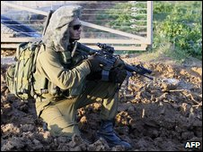 An Israeli soldier kneels as he crosses the border into the Gaza Strip