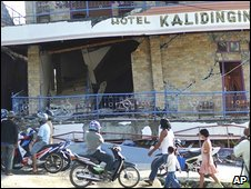 Residents walk past a hotel damaged by earthquakes in Manokwari, Indonesia's Papua province on Sunday