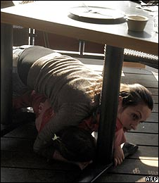 An Israeli mother protects her daughter by hiding under a restaurant table as a Palestinian rocket falls nearby