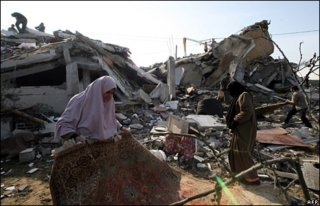 Palestinians go through the remains of their home in the Gaza Strip
