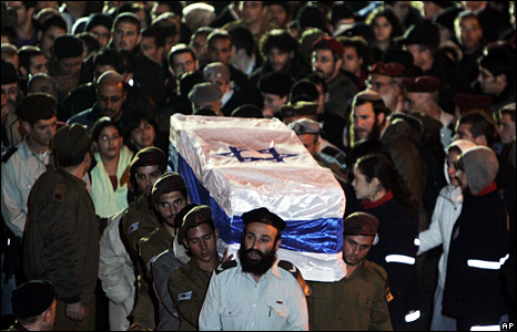 Mourners watch as Israeli soldiers carry the flag-draped coffin of one of their comrades, Sgt Dvir Emanueloff