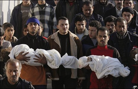 Mourners carry the bodies of three young children said to be have been among the members of a family killed in a shell strike