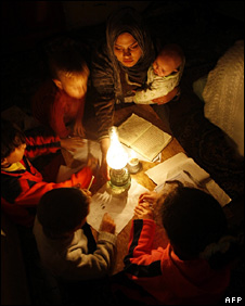 Palestinian children read by gas lamp in Gaza City (1 December 2008)