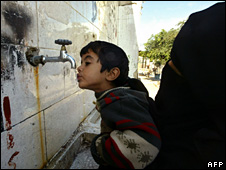 A Palestinian mother helps her son to drink water at the Unrwa headquarters in Rafah (25 November 2008)