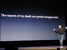 Steve Jobs in front of sign about reports of his death