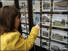 Woman looks in estate agent's window