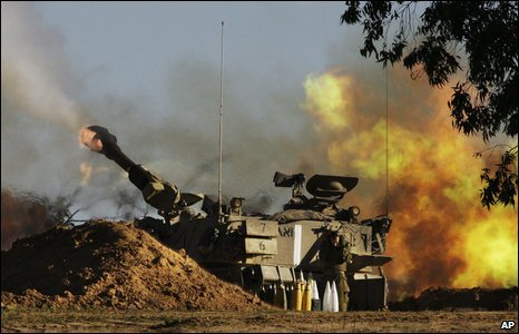 An Israeli Army soldier takes cover as a mobile artillery piece fires towards targets in the southern Gaza Strip on 6 January, 2009