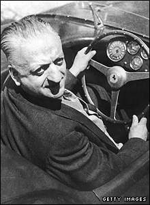 Enzo Ferrari pictured behind the wheel of his car in 1964