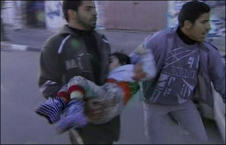 Men carry a child from a school targeted in an Israeli air strike