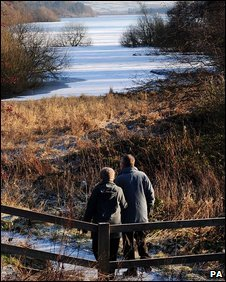 Walkers near the partially frozen Fewston Reservoir, North Yorkshire