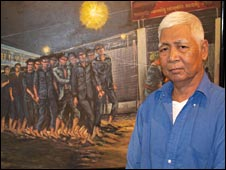 Vann Nath in front of his painting of Tuol Sleng prison