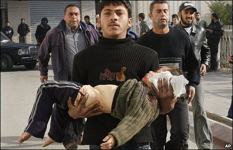 A Palestinian man carries an injured child in Gaza