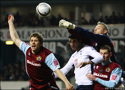Burnley goalkeeper Brian Jensen punches clear