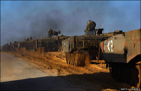 Israeli armoured vehicles head towards the border with Gaza to join the fighting against Hamas militants