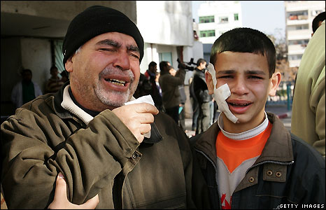 A wounded Palestinian youth and his father at the Shifa hospital in Gaza City