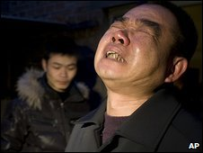 A relative mourns 19-year-old Huang Yanqing, who died of bird flu in China's Hebei province on Monday