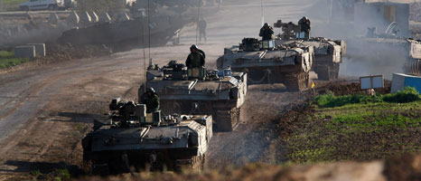 A column of Israeli armoured vehicles leaves their forward base to enter the Gaza Strip