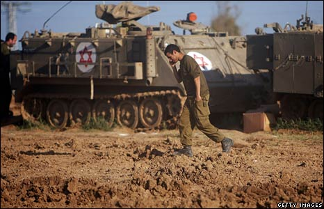 An Israeli soldier speaks on a mobile phone during a three-hour halt in military operations,