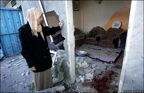 A woman in Gaza inspects damage to a house, 7 Jan 2009
