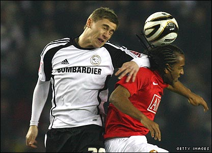 Steve Davies of Derby County goes up for a header with Anderson of Manchester United