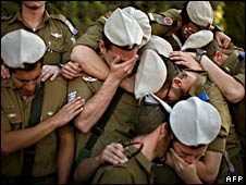 Israeli soldiers mourn over a grave of their colleague killed in Gaza