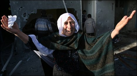A Palestinian woman outside a UN-run school hit by an Israeli missile