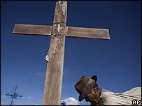 Un campesino boliviano pasa por delante de una cruz